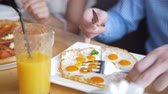 omelete : Male hands cuts a tasty and useful fried eggs with a knife and fork in restaurant Vídeos