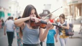 violino : Young caucasian woman playing a fiddle on pedestrian street at summer day Stock Footage