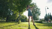 violinista : Young woman playing a violin standing on the grass in the park at sunset
