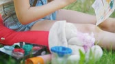 cavalete : Hands of child drawing with brush sitting on the grass at summer Stock Footage