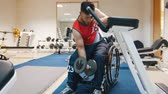 örnekleri : Handsome disabled man in a wheelchair trains in a gym with weights.