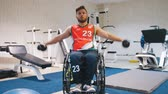 örnekleri : Handsome disabled man in a wheelchair raises his arms with dumbbells in the gym during training.