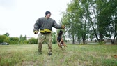 sopa : A man trains his dog to execute jump command and bite his hand