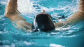 submarino : Disabled man swims on the back in a swimming pool towards the camera. Close up shot. Slow motion