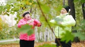 jednota : Mature woman in colourful jackets doing gymnastics in an autumn park after a scandinavian walk
