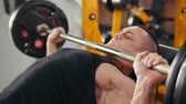 inclinado : Bodybuilder performing incline barbell press exercise on a bench in the gym. Close up