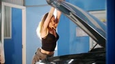 отвертка : Sexy mechanic girl leans on an open car hood