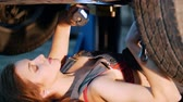 šortky : Sexy mechanic girl lying under the car and repairing it. Close up