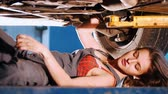 abriu : Sexy mechanic girl lying under the car and repairing it with a wrench. Side angle
