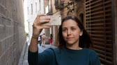 perfumy : Young girl standing at european street and taking a selfie