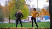 aeróbica : Girls doing gymnastics in the park. Autumn. Fall season