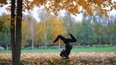 ginasta : Girl doing acrobatic stand on her hands, legs split. Training in autumn park