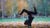 ginasta : Girl doing acrobatic stand on her hands, legs split. Training in autumn park. Close up Vídeos