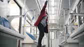 city lifestyle : Young woman dancing in subway train Stock Footage