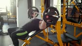 inclinado : Bodybuilder performing incline barbell press exercise on a bench in the gym.