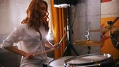 muzycy : Repetition. Redhead girl plays on drums. Slow motion. Focus on drums