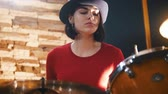 insan grubu : Repetition. Girl in black hat enthusiastically plays the drums Stok Video