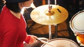criação : Repetition. Girl in black hat plays the drums. Bright lighting