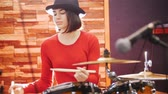 drummer : Girl in black hat enthusiastically plays the drums Stock Footage