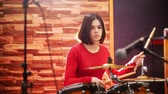 rehearsal : Repetition. Girl in red sweater fervently plays the drums in a studio.