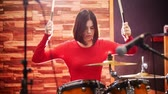 criação : Repetition. Girl in red sweater passionately plays the drums in a studio.