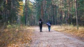 скандинавский : Young woman and a boy on scandinavian walk in the forest. Back view
