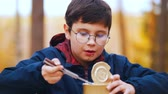 тушеное мясо : A boy in round glasses eating canned stewed meat using a knife Стоковые видеозаписи