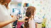 treatment : Stylist makes styling with hairspray for little cute girl Stock Footage