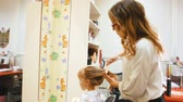 kuaförlük : Hairdresser combs hair for a cute girl. Stok Video