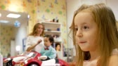 kuaför : Stylist is curling long hair for little cute girl, using electric curling iron. Little boy on background Stok Video