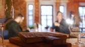 raiz : Two guys sitting at a table in a restaurant and calling the waiter. Pair of glasses in the focus Stock Footage