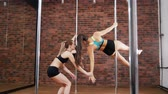 teach : Two women practicing a pose in a pole fitness class with instructor. Dynamic pylon Stock Footage