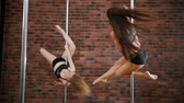 Вы : Two girls practicing a pose in a pole fitness class on the background of brick wall. Dynamic pylon. Slow motion Стоковые видеозаписи