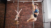 simetria : Two young women practicing a pose in a pole fitness class on the background of brick wall. Dynamic pylon. Slow motion