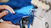 costuming : Making clothes. Woman works with textile on Sewing Machine. Focus on cloth