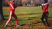 бегун : Two young woman in sport costumes doing leg lunges in park Стоковые видеозаписи