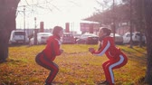 workout : Two young woman in sport costumes doing squats in park Stock Footage