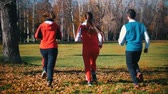 бегать трусцой : Young people running in the park. Back view. Slow motion