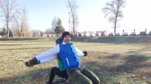 поднимать : Young man and a woman are warming up in late autumn park. Doing squats on open air back to back. Стоковые видеозаписи