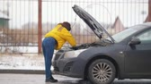 automóveis : Car Trouble. Winter, cold weather. A young woman opens the hood, looking inside, rummaging in the engine, holding a phone Vídeos
