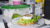 сердечный : Healthy breakfast. Making a sandwich with fried egg and avocado. Pouring the sauce