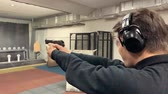 arma curta : Man aims, holding a gun at a shooting gallery, shooting range.