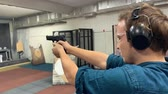 pistole : Young man aims, holding a gun at a shooting gallery, shooting range. Slow motion