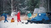 śnieżka : Winter forest. Family in colorful clothes playing snowballs in slow motion. Snowmobiles on the foreground. Wideo