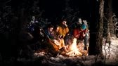 chilling : Young people in the winter forest sitting by the fire. Frying food on the fire Stock Footage