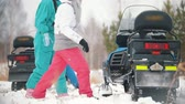 śnieżka : Young people in bright clothes getting on the snowmobiles. Slow motion