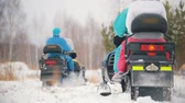 wintersport : Young people in bright clothes getting on the snowmobiles. Starting a speed race. Slow motion