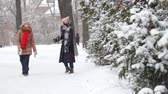 duas pessoas : Two girls in winter walking and talking with each other. Hugging