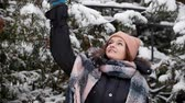 ель : Cheerful young woman shakes a branch and snow falls from trees