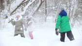 wintertime : Winter forest. Happy children standing in front of each other playing snowballs Stock Footage